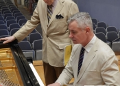 Melvin Stecher observes Ron Losby checking the Steinway on stage